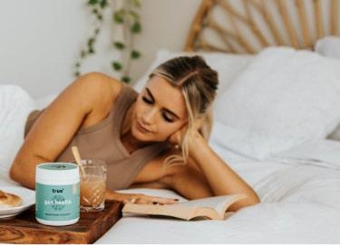 Girl Reading Next to True Gut Health