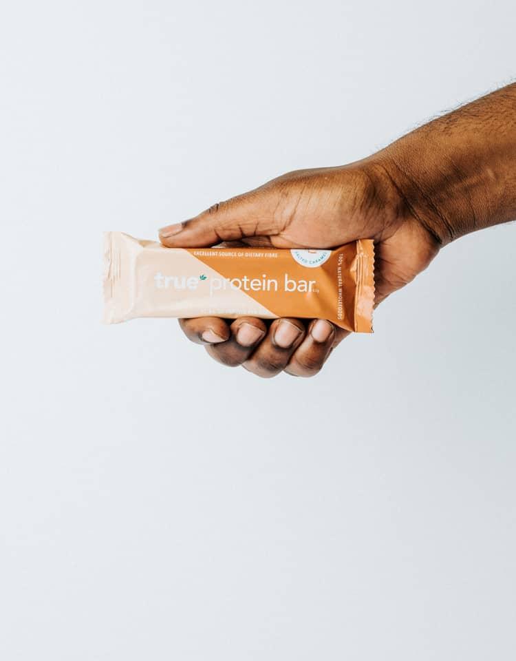 Hand Holding True Protein Bar